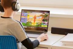 Vilnius, Lituania - 2 marzo 2019: Bambino che gioca il gioco di Fortnite Fortnite è video gioco online popolare sviluppato dall'e fotografie stock libere da diritti