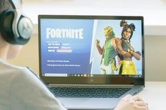 Vilnius, Lituania - 2 marzo 2019: Ragazzo che gioca il gioco di Fortnite Fortnite è video gioco online popolare sviluppato dall'e fotografia stock libera da diritti