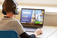 Vilnius, Lituania - 2 marzo 2019: Ragazzo che gioca il gioco di Fortnite Fortnite è video gioco online sviluppato da Epic Games fotografia stock