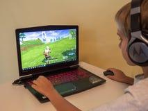 Vilnius, Lituania - 12 novembre 2018: Ragazzo che gioca Fortnite Fortnite è video gioco online sviluppato da Epic Games immagini stock libere da diritti