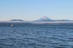 Vilyuchinsky火山的看法也叫从游船的维柳钦斯基火山 云彩在沿海峭壁说谎 免版税库存图片