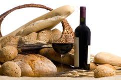 Vin avec du pain d'isolement sur le blanc Images stock