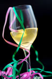 Vin blanc dans un verre avec des rubans et un fond noir Images stock