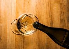 Vin blanc de versement dans un verre à vin Photographie stock