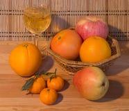 Vin blanc fait maison et fruit mûr sur une table en bois Image stock