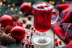 Vin brulé caldo del mirtillo rosso di Natale, perforazione arancio del melograno o sangria closeup Scavi il pupazzo di neve Immagini Stock