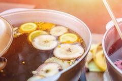 Vin brulé pronto in vaso del ferro alla fiera della via della città Bevanda tradizionale dell'alcool del nuovo anno e di natale - fotografia stock