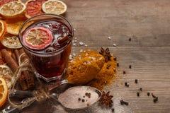 Vin brulé, spezie e frutti secchi su una tavola rustica fotografie stock