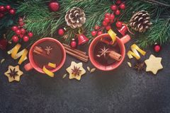 Vin brulé in tazze rosse e nel fondo festivo di Natale Immagine Stock