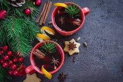 Vin brulé in tazze rosse e nel fondo festivo di Natale Fotografia Stock
