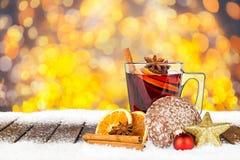 Vin chaud épicé chaud sur les planches neigeuses en bois Photo stock