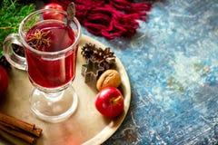 Vin chaud avec des pommes, des écrous et des épices sur le plateau de cuivre photos stock