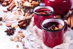 Vin chaud chaud dans une tasse rouge pendant des vacances d'hiver Images stock