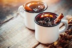 Vin chaud dans des tasses rustiques blanches avec des épices Photos libres de droits