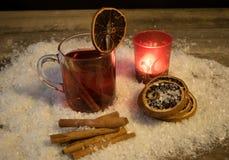 Vin chaud dans la neige par lueur d'une bougie photo stock