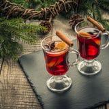 Vin chaud de Noël avec de la cannelle et l'orange sur le conseil rustique en bois Boisson chaude traditionnelle à l'époque de Noë image stock