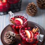Vin chaud en verres sur un fond en bois Pommes, canneberges, cannelle, anis d'étoile images stock