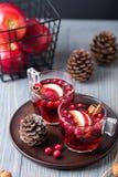 Vin chaud en verres sur un fond en bois Pommes, canneberges, cannelle, anis d'étoile photo stock