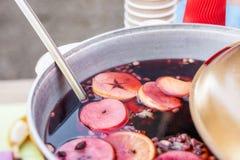 Vin chaud préparé dans le pot de fer à la foire de rue de ville Boisson traditionnelle de Noël et d'alcool de nouvelle année - vi photos stock