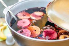 Vin chaud préparé dans le pot de fer à la foire de rue de ville Boisson traditionnelle de Noël et d'alcool de nouvelle année - vi photographie stock libre de droits