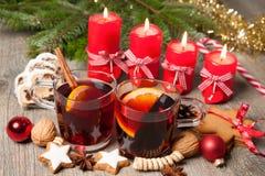 Vin chaud rouge sur la table avec les bougies brûlantes Images stock