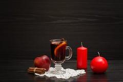 Vin chauffé avec des épices Bougies, bâtons de cannelle et pomme blA Image stock