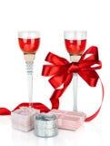 Vin dans des deux verres à vin avec la proue de satin et l'isolat rouges de boîte-cadeau Images stock