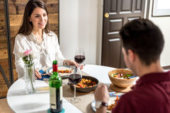 Vin de consommation et potable de jeunes couples heureux à la maison image stock