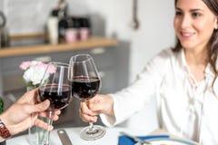 Vin de consommation et potable de jeunes couples heureux à la maison et grillant avec du vin Photographie stock libre de droits