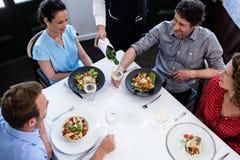 Vin de portion de serveur au groupe d'amis tout en prenant le déjeuner Image libre de droits