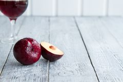 Vin de prune dans le verre et la prune avec la moitié coupée sur le fond en bois Image stock