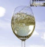 Vin de versement dans un verre de vin Photo libre de droits