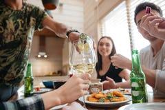 Vin de versement de personnes dans le verre et le dîner de avoir avec des amis Image libre de droits