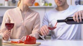 Vin de versement de mari dans des verres et donner à l'épouse, couple faisant cuire ensemble banque de vidéos