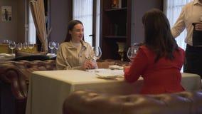 Vin de versement de serveur dans le verre de la fille dans le restaurant Deux amies positives s'asseyant dans le confortable clips vidéos