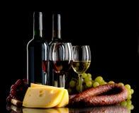 Vin, druvor, ost och korv på svart bakgrund Royaltyfria Foton