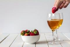 Vin et fraises de chute en verre sur le Tableau avec l'espace de copie Image stock