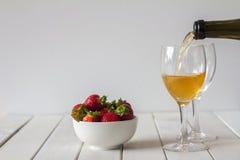 Vin et fraises de versement sur le Tableau avec l'espace de copie Photographie stock