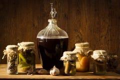 Vin fait maison dans le garde-manger avec des légumes photographie stock libre de droits