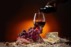 Vin flödar från flaskan in i exponeringsglaset arkivfoto