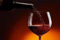 Vin från flaskan flödar in i exponeringsglaset royaltyfria bilder