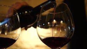 Vin från flaskan hälls in i ett exponeringsglas arkivfilmer