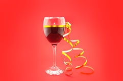 Vin i exponeringsglas med det guld- bandet på röd bakgrund Royaltyfria Bilder