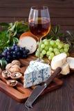 Vin i exponeringsglas med druvan och ost på träbakgrund arkivbilder