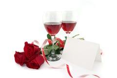 Vin i exponeringsglas, röda rosor, band och det tomma kortet för ett meddelande Royaltyfri Bild
