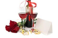 Vin i exponeringsglas, röda rosor, band och tomt kort som isoleras Arkivbild