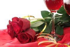 Vin i exponeringsglas, röda rosor och band på rött och vitt Arkivbild