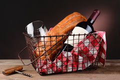 Vin och bröd i trådpicknickkorg arkivfoton