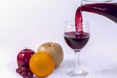 Vin och frukt på vit bakgrund Royaltyfri Foto