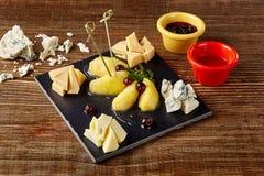 Vin- och ostplatta - fyra sorter av ost, päron, honung Utmärkt aptitretarevin arkivbilder